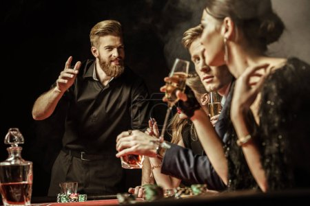 Photo for Side view of men and women playing poker in casino - Royalty Free Image