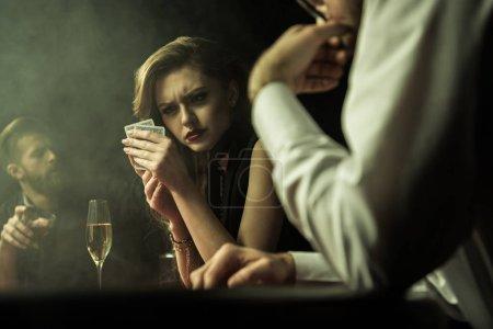 Foto de Vista lateral de mujer concentrada jugando al poker con cartas en las manos - Imagen libre de derechos