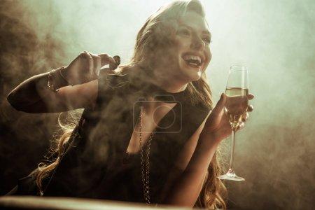 Foto de Retrato de mujer riendo con la bebida y poker chip en manos - Imagen libre de derechos