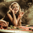 Portrait of smiling woman with drink and poker chi...