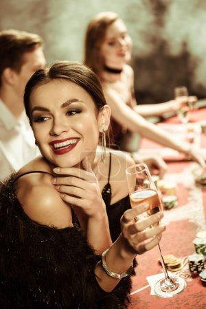 Photo for Portrait of smiling woman with drink playing poker - Royalty Free Image