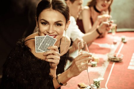 Photo for Portrait of smiling woman with drink and cards playing poker - Royalty Free Image