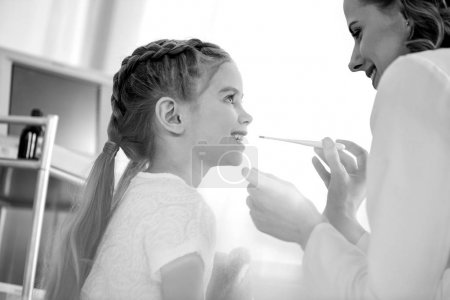 Photo for Side view of doctor measuring temperature of smiling girl, black and white photo - Royalty Free Image