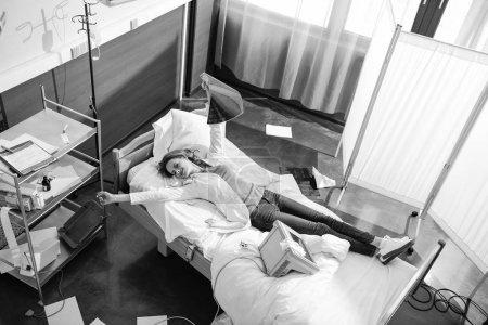 Photo pour Vue grand angle du médecin avec image radiographique couchée sur le lit d'hôpital, photo noir et blanc - image libre de droit