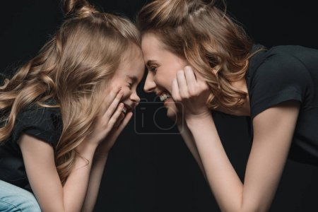 Photo for Portrait of stylish daughter and mother smiling, touching foreheads and looking at each other isolated on black - Royalty Free Image