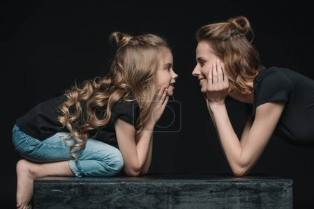 Foto de Side view of stylish daughter and mother smiling and looking at each other isolated on black - Imagen libre de derechos