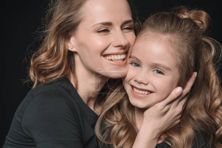 Photo for Portrait of stylish daughter and mother smiling and hugging isolated on black - Royalty Free Image