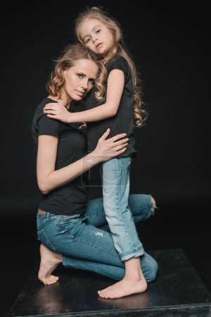 Photo for Side view of stylish daughter and mother hugging isolated on black - Royalty Free Image