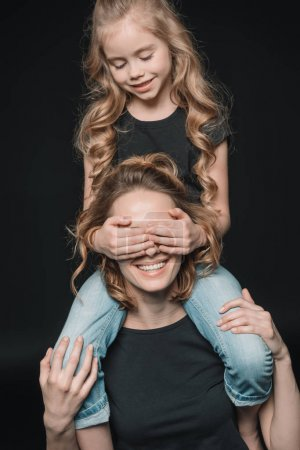 daughter sitting on mother's shoulders
