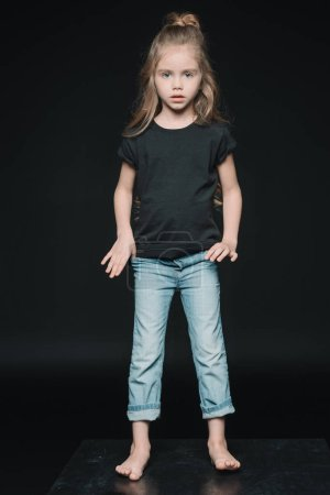 Photo for Stylish adorable girl standing and looking at camera isolated on black - Royalty Free Image