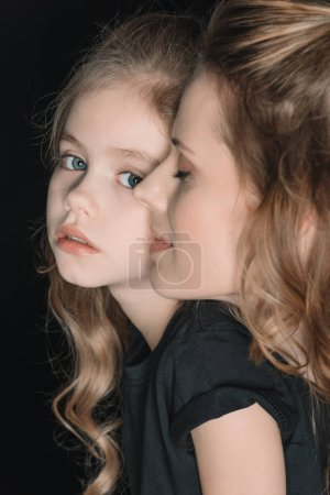 Photo for Portrait of adorable daughter and mother isolated on black - Royalty Free Image