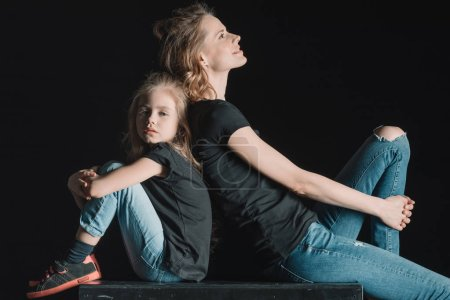 Photo for Side view of stylish mother and daughter sitting on cube  isolated on black - Royalty Free Image