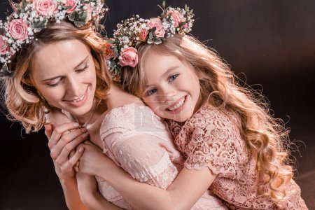 Photo for Portrait of hugging daughter and mother in flowers wreathes on black - Royalty Free Image
