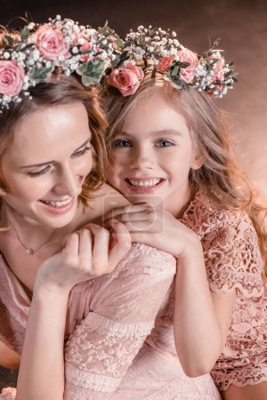 Photo for Portrait of cheerful hugging daughter and mother in flowers wreathes - Royalty Free Image