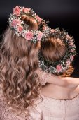 Mother and daughter in flowers wreathes