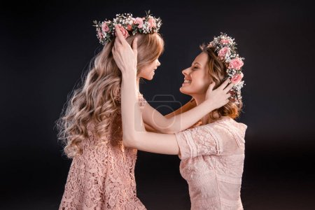 Photo for Side view of smiling mother and daughter in flowers wreathes  isolated on black - Royalty Free Image