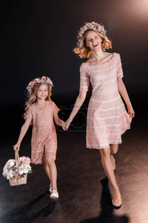 Photo for Happy mother and daughter in floral wreaths walking with flower basket - Royalty Free Image