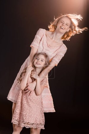 Photo for Beautiful mother and daughter in pink dresses hugging and smiling at camera  isolated on black - Royalty Free Image