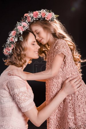 Photo for Happy mother and daughter in floral wreaths hugging and touching foreheads isolated on black - Royalty Free Image