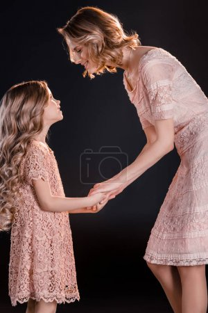 Photo pour Beautiful mother and daughter holding hands and looking at each other isolated on black - image libre de droit