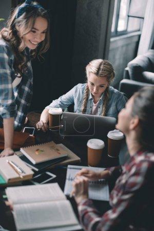 Photo pour Belles filles étudiants boire du café et étudier ensemble au bureau - image libre de droit