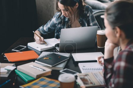 Photo for Concentrated young woman student using laptop and writing while sitting near colleague - Royalty Free Image