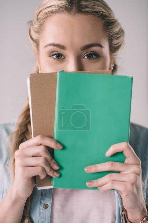Photo pour Portrait d'une étudiante couvrant le visage avec des cahiers dans les mains - image libre de droit