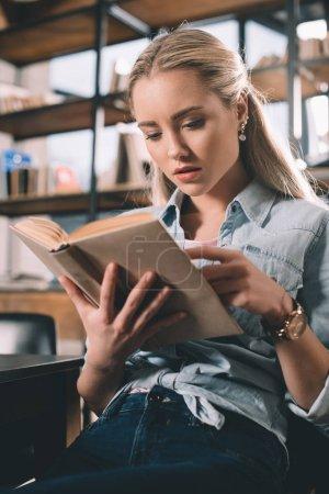 Photo pour Portrait de femme concentré étudiant lecture livre dans la bibliothèque - image libre de droit