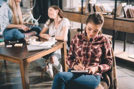 Photo pour Femme et rédige une étude de cahier avec deux étudiants derrière - image libre de droit