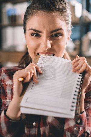 girl biting copybook