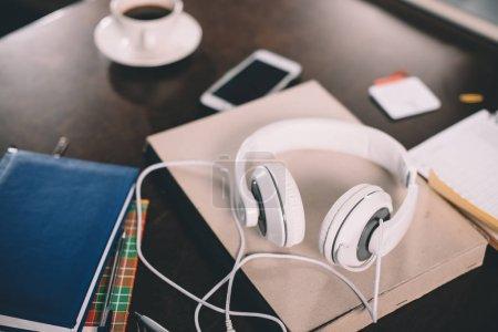 Photo pour Livre, smartphone, tasse de café, copybooks et écouteurs sur la table - image libre de droit