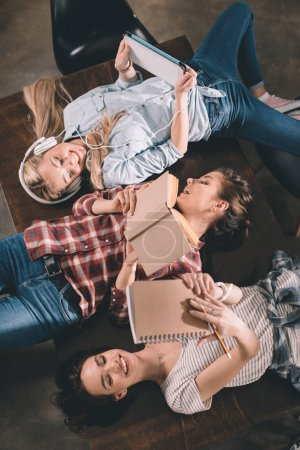 Photo for Smiling students studying together and lying on table - Royalty Free Image