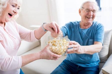 Senior couple eating popcorn