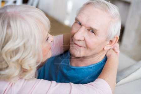 Photo for Happy senior couple embracing at home, man looking at camera - Royalty Free Image
