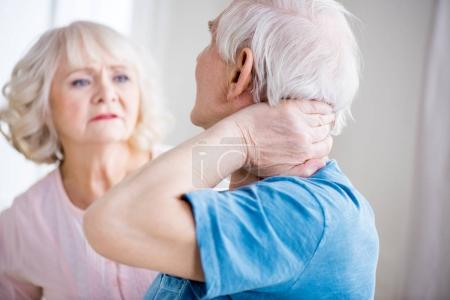Photo for Back view of man with neck pain and concerned woman at home - Royalty Free Image