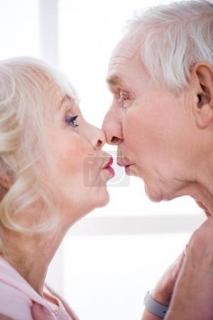 Photo pour Vue latérale du couple heureux de personnes âgées embrassant à la maison - image libre de droit
