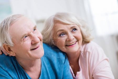 Photo pour Embrassant couché heureux couple de personnes âgées et à la recherche de suite à domicile - image libre de droit