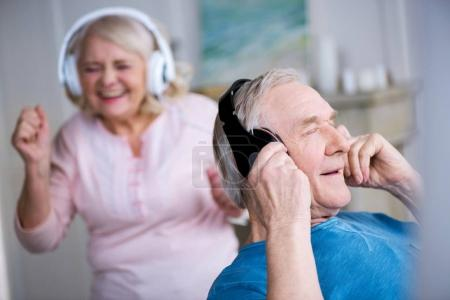 Photo pour Heureux couple de personnes âgées dans les écouteurs s'amuser ensemble à la maison - image libre de droit