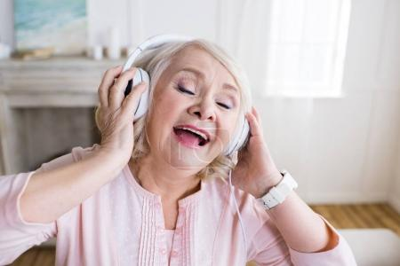 Photo for Happy senior woman with closed eyes wearing headphones and singing - Royalty Free Image