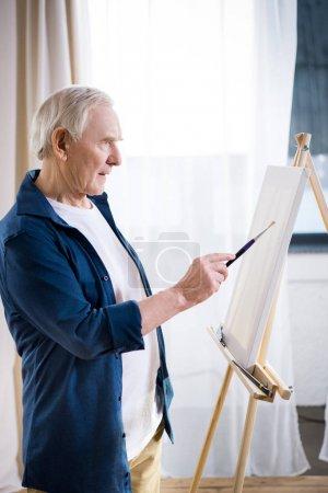 Photo pour Vue de côté de photo peinture homme senior concentré sur chevalet à la maison - image libre de droit