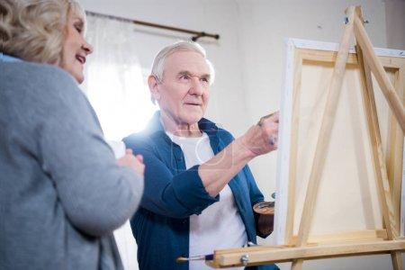 Photo pour Photo peinture heureux couple de personnes âgées sur chevalet à la maison - image libre de droit