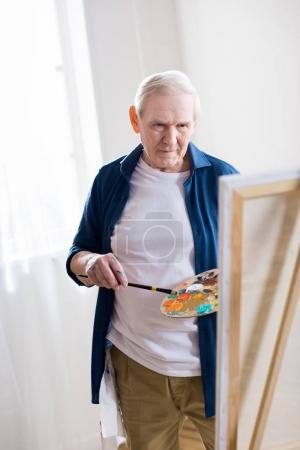 Photo pour Portrait d'un homme senior concentré, dessin en atelier d'art - image libre de droit