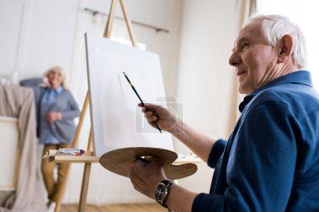 Photo pour Homme senior sérieux dessin portrait de femme en atelier d'art - image libre de droit