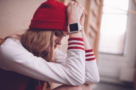 Photo pour Femme hipster élégant bouleversé avec smartwatch assis et regardant vers le bas - image libre de droit