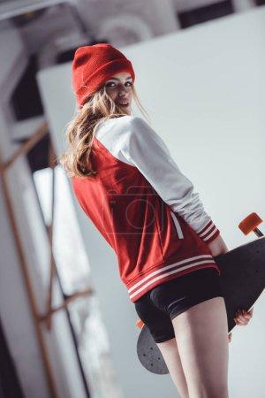Photo pour Femme hipster élégante avec longboard posant en studio sur gris - image libre de droit