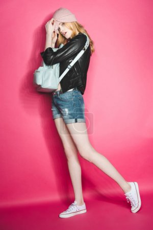 Photo for Stylish hipster woman in leather jacket with backpack on pink - Royalty Free Image