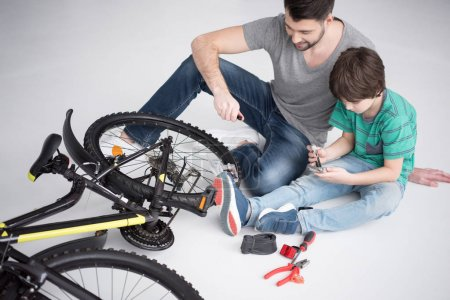 father and son repairing bicycle