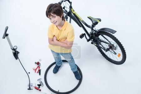 Photo for Top view of smiling boy standing inside tire near bicycle on white - Royalty Free Image