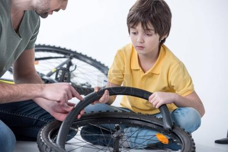 Photo for Son and father repairing bicycle tire in studio on white - Royalty Free Image