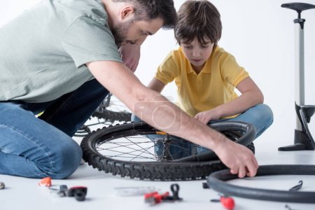 Son and father repairing bicycle